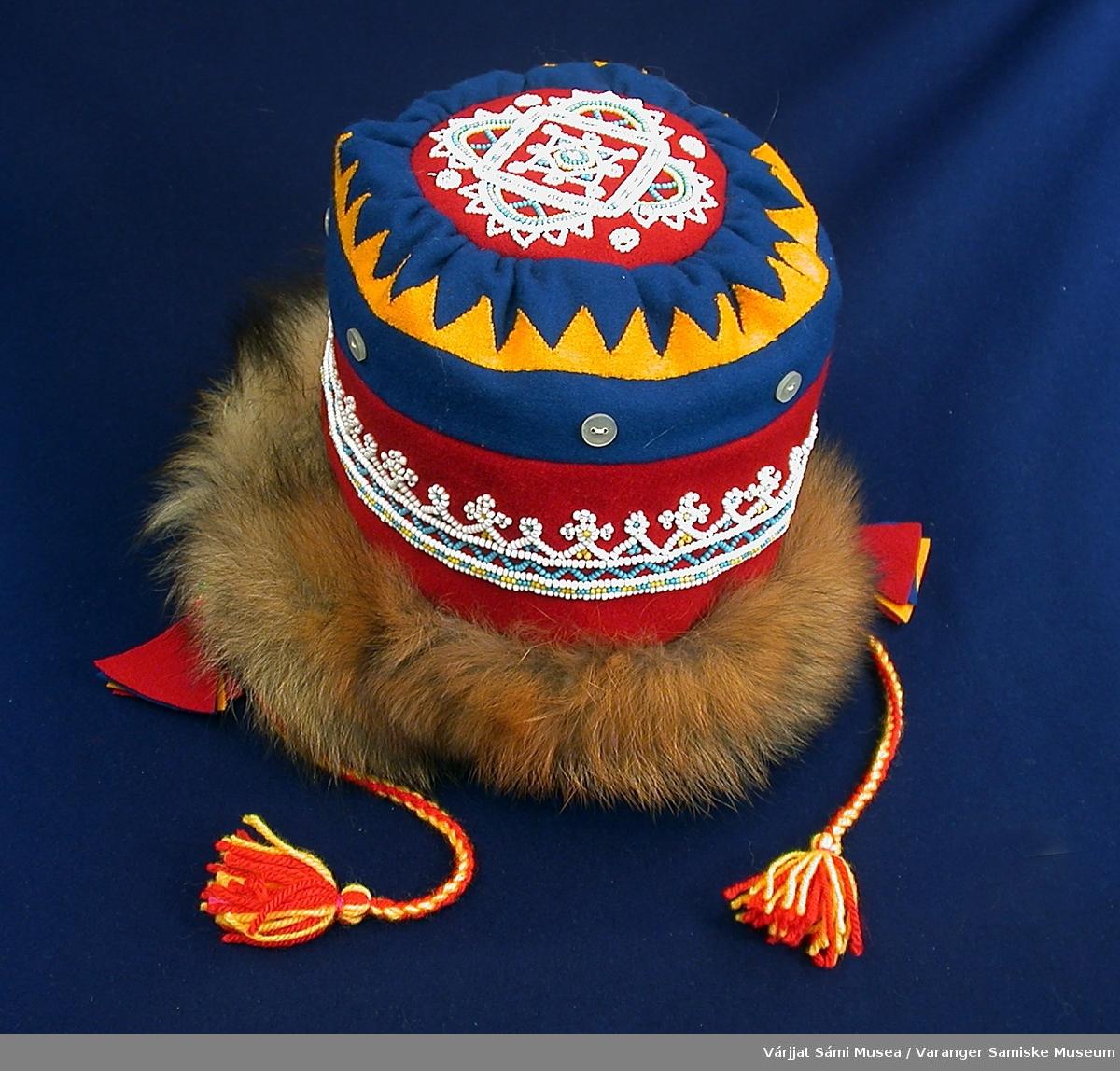 Jentelue av klede og reveskinn dekorert med perler og knapper. Kledet er i rødt, blått og gult, hvorav det gule utgjør en del av dekorasjonen i form av et sik-sak-bånd. Perlebroderiene er av små glassperler i hvitt, gult og lyseblått. Det ene broderiet går som et bånd rundt hele lua, det andre er en stor rose på toppen av lua.. Rundt lua, over perlebåndet og soom en del av rosemotivet, er det sydd fast halvblanke, hvite knapper. Lua er kantet med reveskinn nederst, nærmest ansiktet. Lua knyttes under haka med tvunnede snorer av ullgarn i gult og rødt. I enden av snorene er det dusker av samme garn. I andre enden av snorene, der de er festet til lua, henger det en dusk på hver side laget av klede i rødt og gult.
