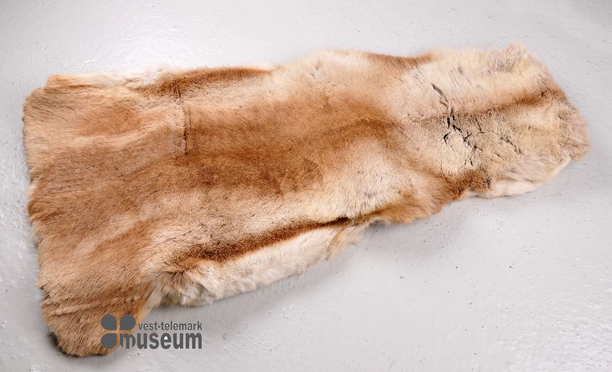 Reinsyrfell der det på undersida av halsstykket er sydd ei lomme til å stikke føtene inn i. Elles er fellen naturleg forma.