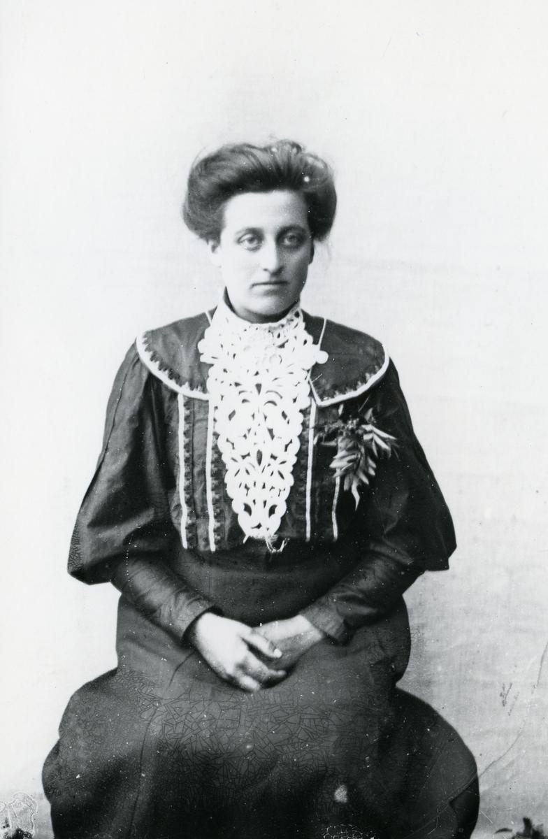 Kvinne sittende foran lerret