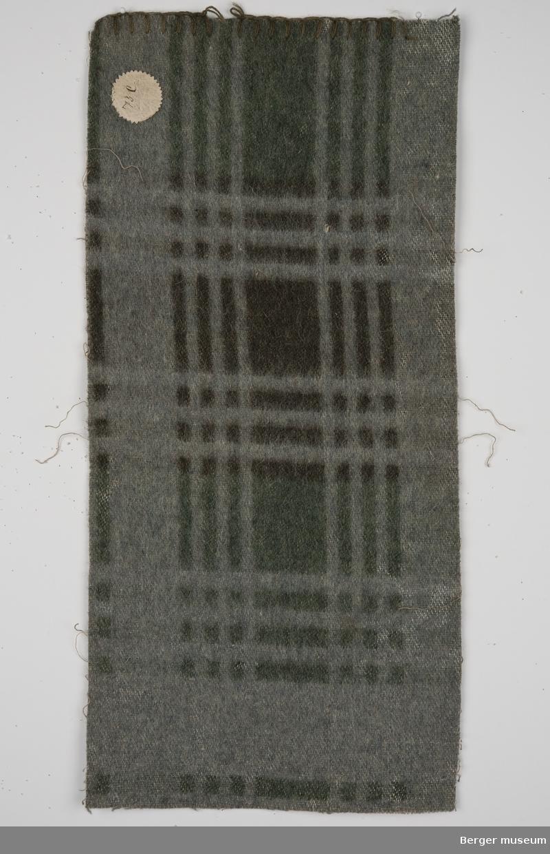 En prøve. Grå bunn, grønne og svarte striper i et rutemønster. En bred stripe i midten i lengderetning og tre smale striper på begge sider.