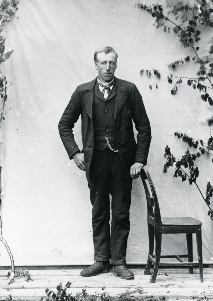 Dresskledd mann i helfigur, ved stol, lerretbakgrunn