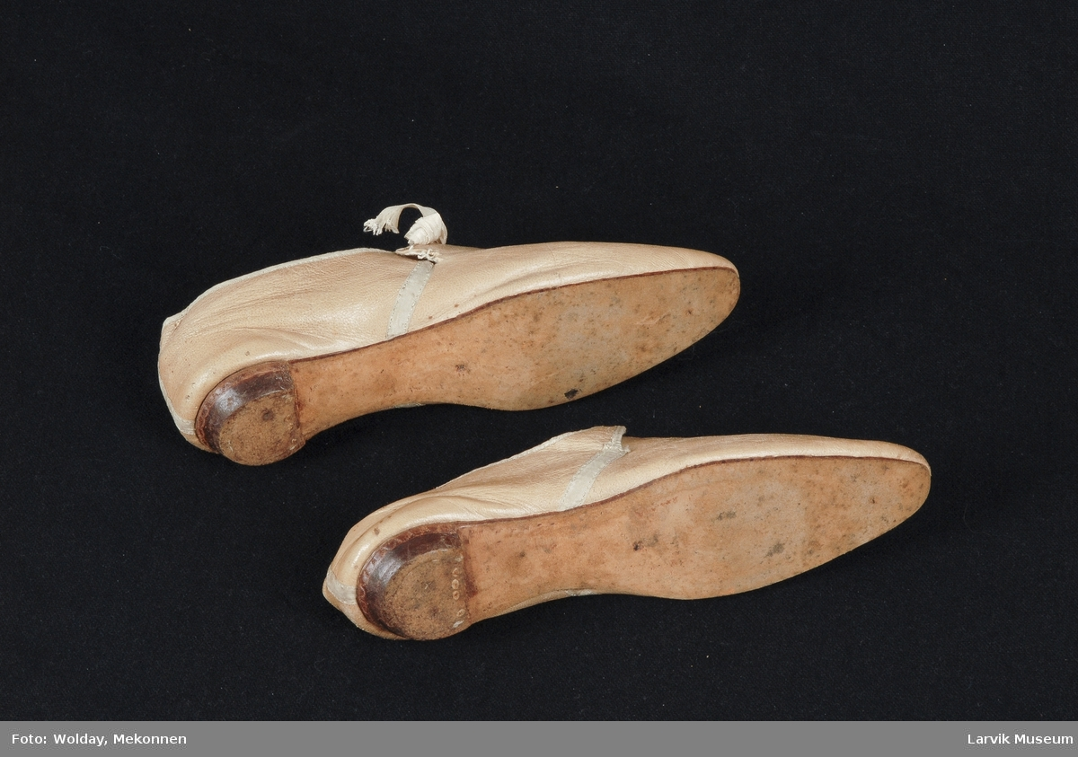 Form: beige lær/silkebånd/lerretsfór og innersåle av lær/såle + hål av lær/treplugger/likesidete såler/moderatvspiss tupp/smal såleform/forstykkets overlær er midt på 12,8 cm langt, uten pløse/bakstykket søm m.b. og klippet m smale snipper over vristen som har hull m silke- bånd til sløyfe midt på (mangler). Sømmene er dekket m bånd/ oppbyggethæl, sydd og plugget.