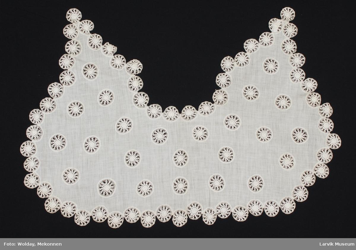 Form: Et stykke med innfeldte blonder i sirkler, resten i tynt stoff, på hver side går det to felter ned.