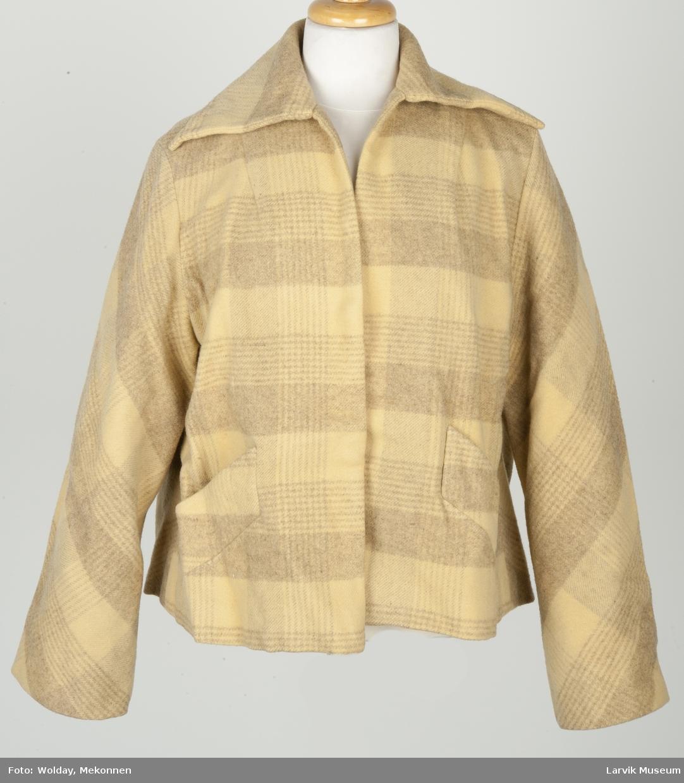 Kort jakke med krave, lommer og lange ermer. Ruter i gule og lyse brune farger.