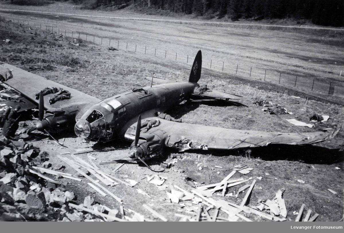 Tyske soldater hviler på og rundt vraket av et bombefly av typen Heinkel 111.