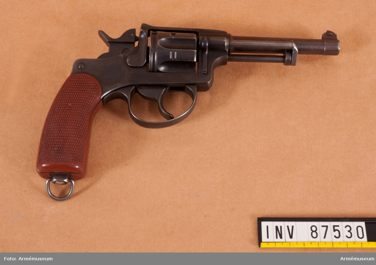 Revolver i svart schatull klätt med röd sammet, med samhörande skruvverktyg.