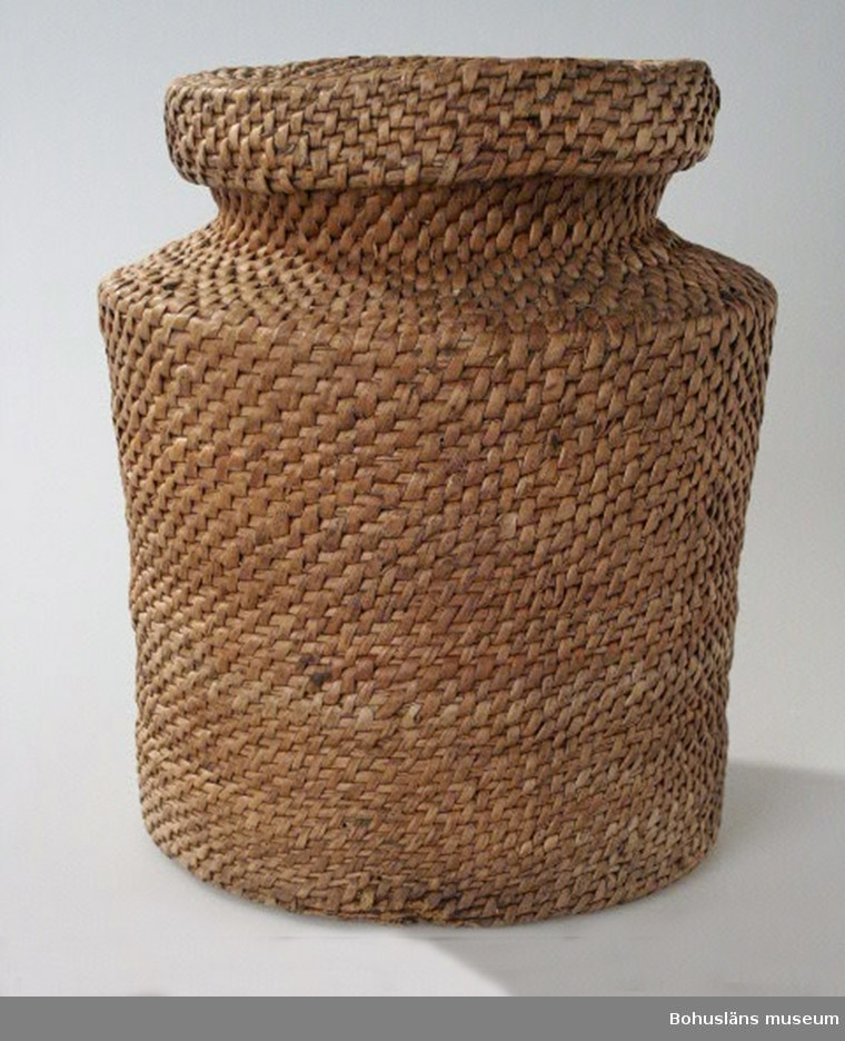 Cylindriskt kärl. Upptill smalnar det tvärt av. Kort hals och rund öppning vilken är 15,5 cm. Över öppningen är det ett platt lock. Användes till förvaring av torkade nypon.  Tillverkaren/brukaren är född Johansson. Givaren är född 1907 i Kålsby, Skredsviks socken, och är dotter till tillverkaren Emma Karlsson.