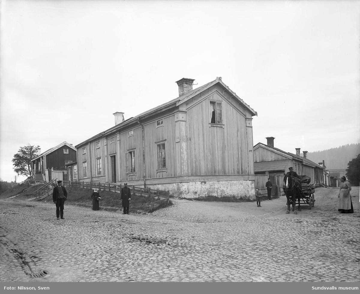 """Östbergska gården och längst tillvänster Gesällhärberget även kallat """"Luffarhärberget"""" efter västra delen av Storgatan. Man med hästkärra efter Holmgatan. Byggnaderna finns nu bredvid varandra på Norra Berget."""