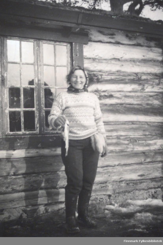Anne Marie Nymo står utenfor en hytte som kan være skogvokterhytta i Rochi og holder en liten fisk i hånda.