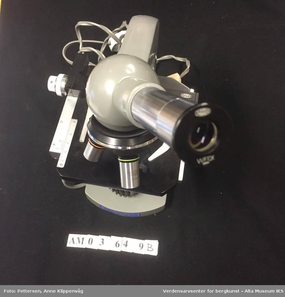A: Trekasse, med bæreåndtak festet på oversiden. Inneholder et mikroskop, en ekstra trebunn som beskytter mikroskopet, og en liten trekasse med ekstradeler til mikroskopet. Kassen står på fire gummiknotter.   B. Mikroskop. Et grålakkert mikroskop, av merket Olympus. Elektrisk, med innebygget lampe.