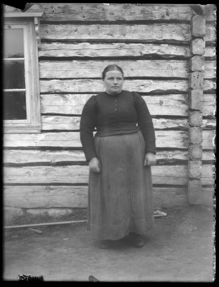 Kvinne foran husvegg
