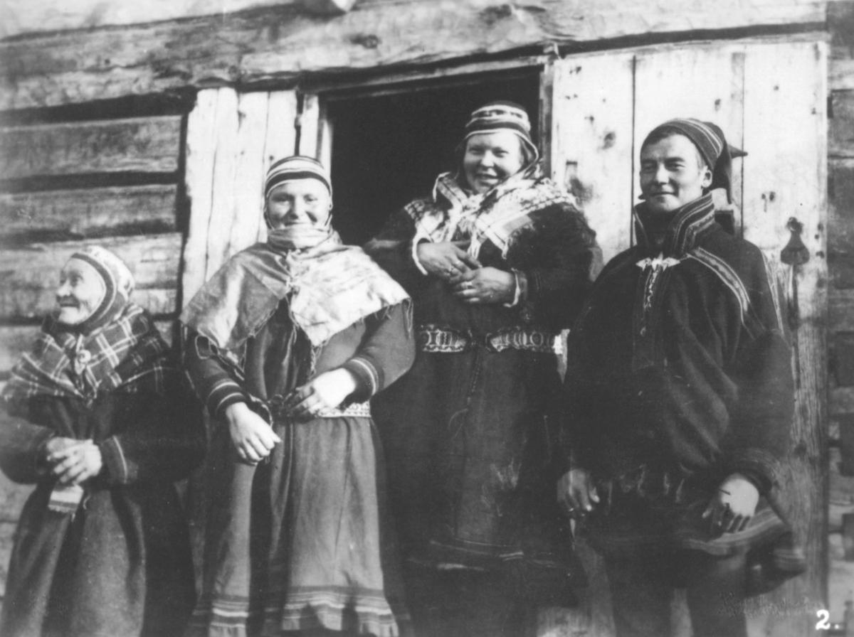 Bilde nr. 2 i serien '10 amatørbilleder fra lappernes hjem og liv i Finnmark', se FB 93164-001. 'Kautokeino lapper.'  Tre kvinner og en mann utenfor et hus. De er kledt i samekofter og luer. Kvinnene har på seg sjal.