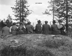 Gruppe med åtte menn, fotografert sittende på en rund bergna