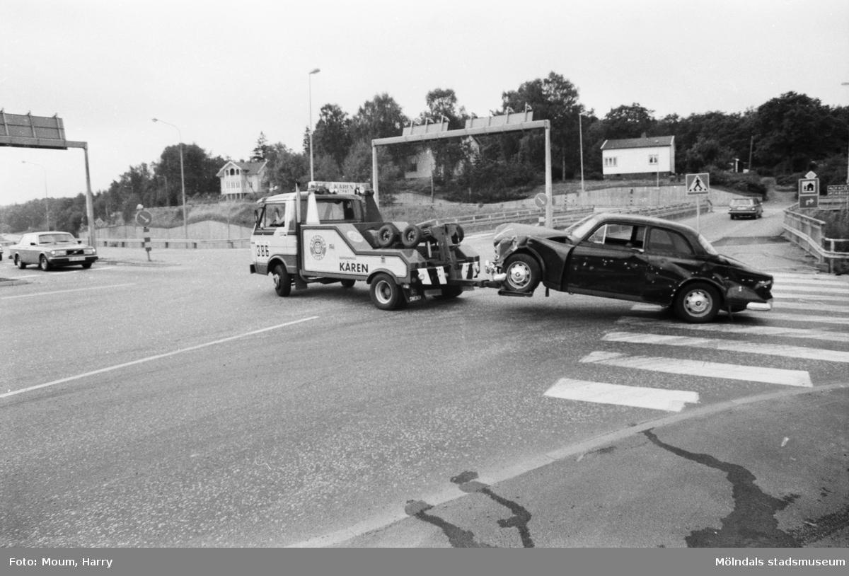 """Krockad bil bogseras bort från IKEA-motet i Kållered, år 1983. """"En tyvärr alltför vanlig syn i korsningen vid IKEA-motet.""""  För mer information om bilden se under tilläggsinformation."""