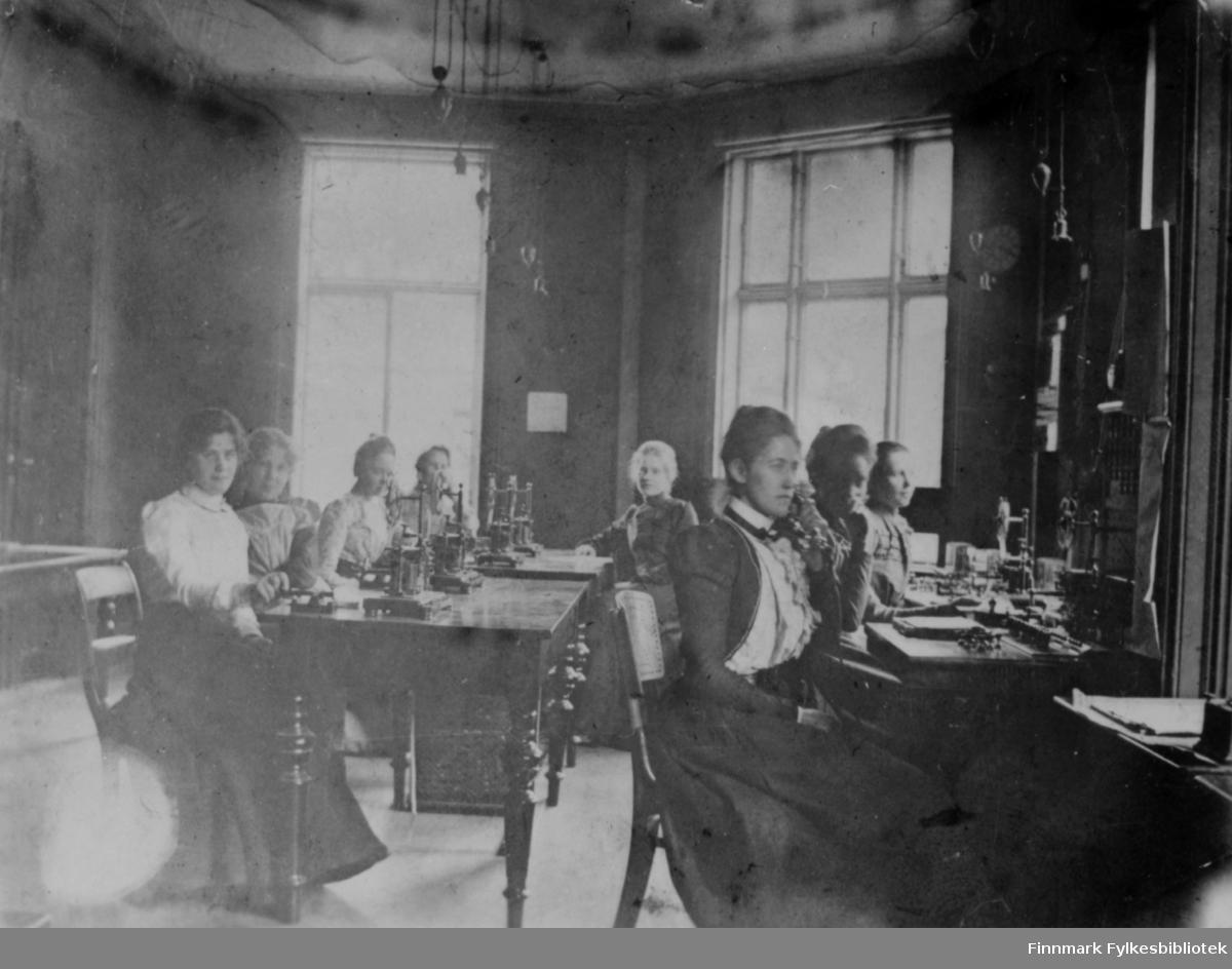 Åtte kvinner sitter ved arbeidsbordene sine ved telegrafekspedisjonen i Hammerfest. Alle er kledd i lange kjoler og har telegrafsender foran seg, også kalt morsenøkkel eller telegrafnøkkel.