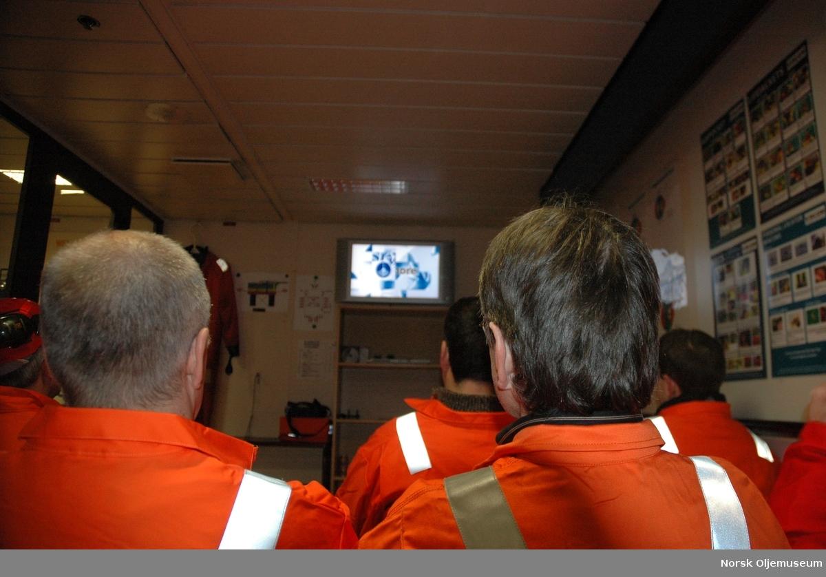 En gruppe mennesker ser på en presentasjon på en tv i et møterom ...