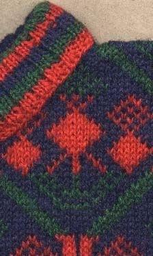 Bingestickad Tröja i 2-trådigt ullgarn. Rött och grönt Bjärbomönster på blå botten. Ärmen enfärgad med en bård av bjärbomönstret längst ned. Nederkant bål, ärmmuddar och halskant resårstickade i randning rött.grönt och blått.