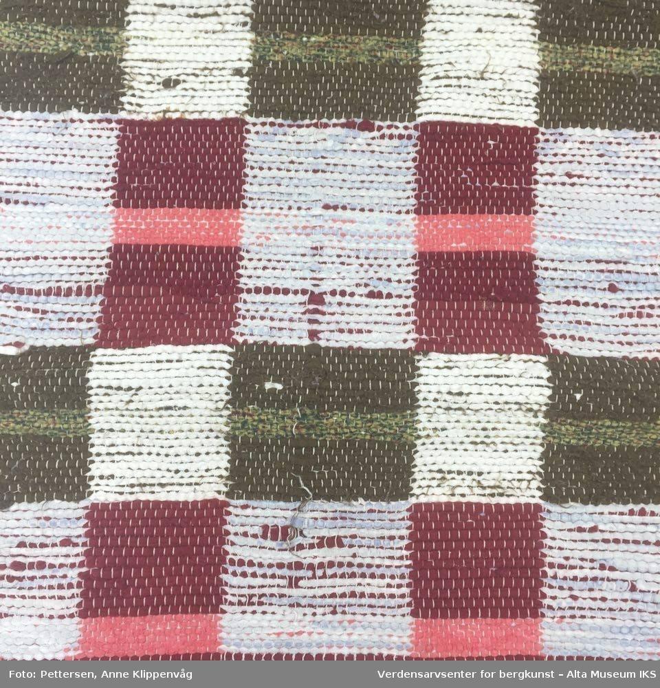 Rektangulær fillerye med ulike farger. Rutemønstret, med hvite rysjer på hver kortende.