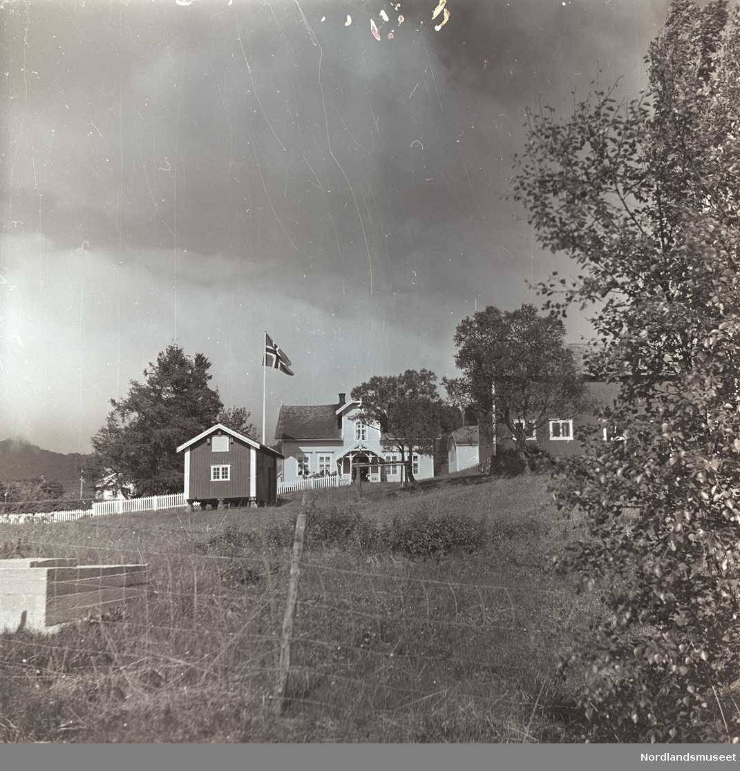 I forgrunnen bak nettinggjerde eng, et tre til høyre. Midt i bildet et hvitt hus med ark og bislag bak stakittgjerde. Stort tre ved siden av huset og flaggstang med det norske flagg foran. Litt foran, to bygninger. Sommer.