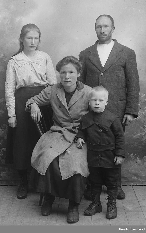 Portrett. Familiebilde. 4 personer. Foran sitter mora, i 30-åra. Ved hennes side står en gutt, ca. 5 år. Bak står faren, i 30-åra. Ved hans side står ei jente ca. 12-15 år.