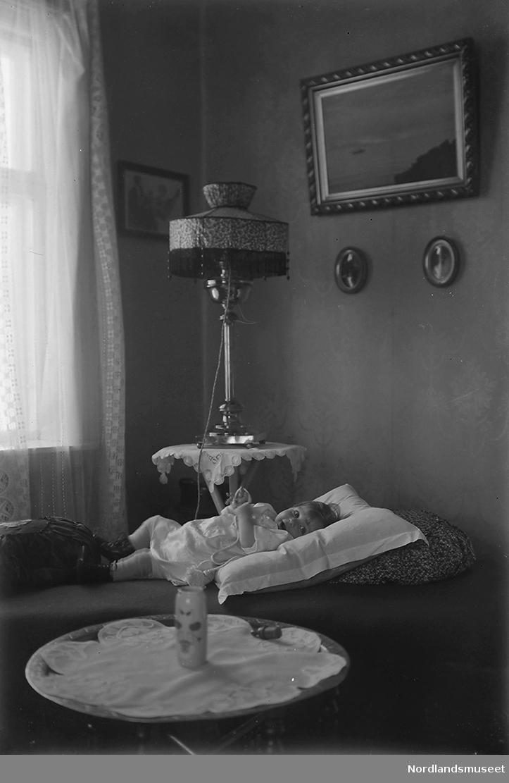 """Et pikebarn ligger på en divan. Barnet kan være Else """"Lillemor"""" Lund eller Anders Forsdahls første barnebarn. Bildet er sannsynligvis tatt i Sulitjelma."""