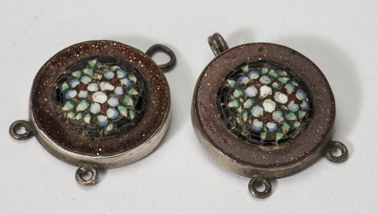 Hekte hvor dekoren er tre små blomster og grønne blad laget i en minimosaikk. Rundt denne en kobberfarget sirkel.