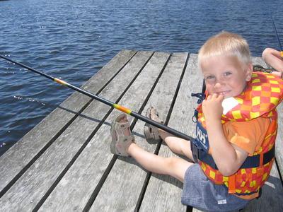 gutt som sitter på ei brygge og fisker