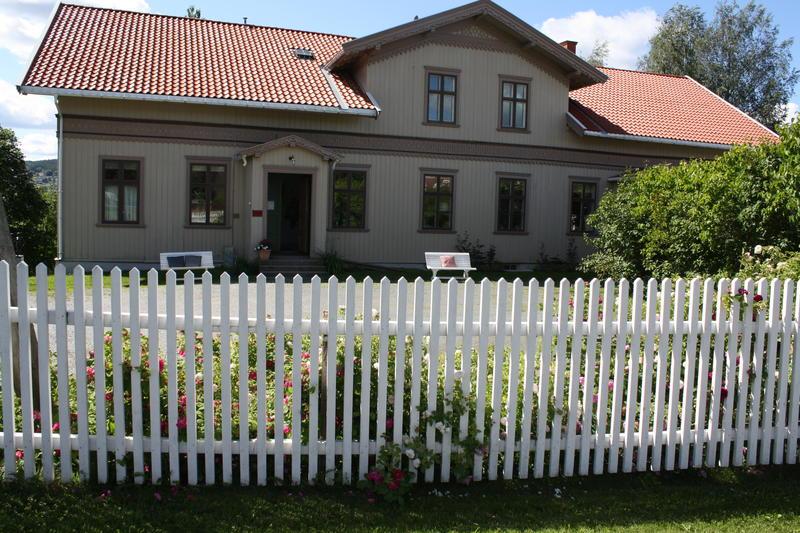 Inngangspartiet Kvinnemuseet med stakittgjerdet og rosebed. Sommerdag med solskinn