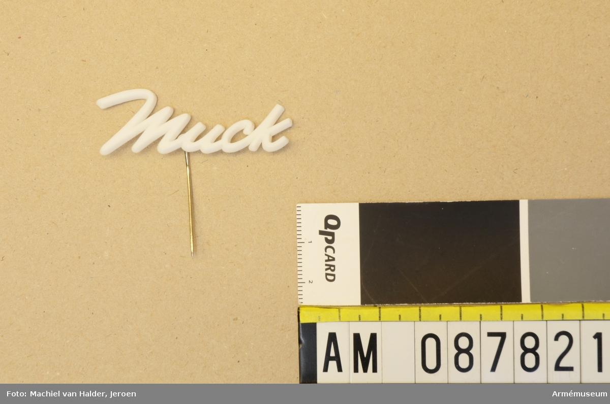 """Vit pin i form av ordet """"Muck"""", tillverkad i plast med nål i metall."""