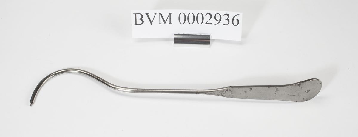 Instrument med en flat ende og en krum ende med et spor. Sonden er bøyd for å passe til urinrørets krumning hos mannen.