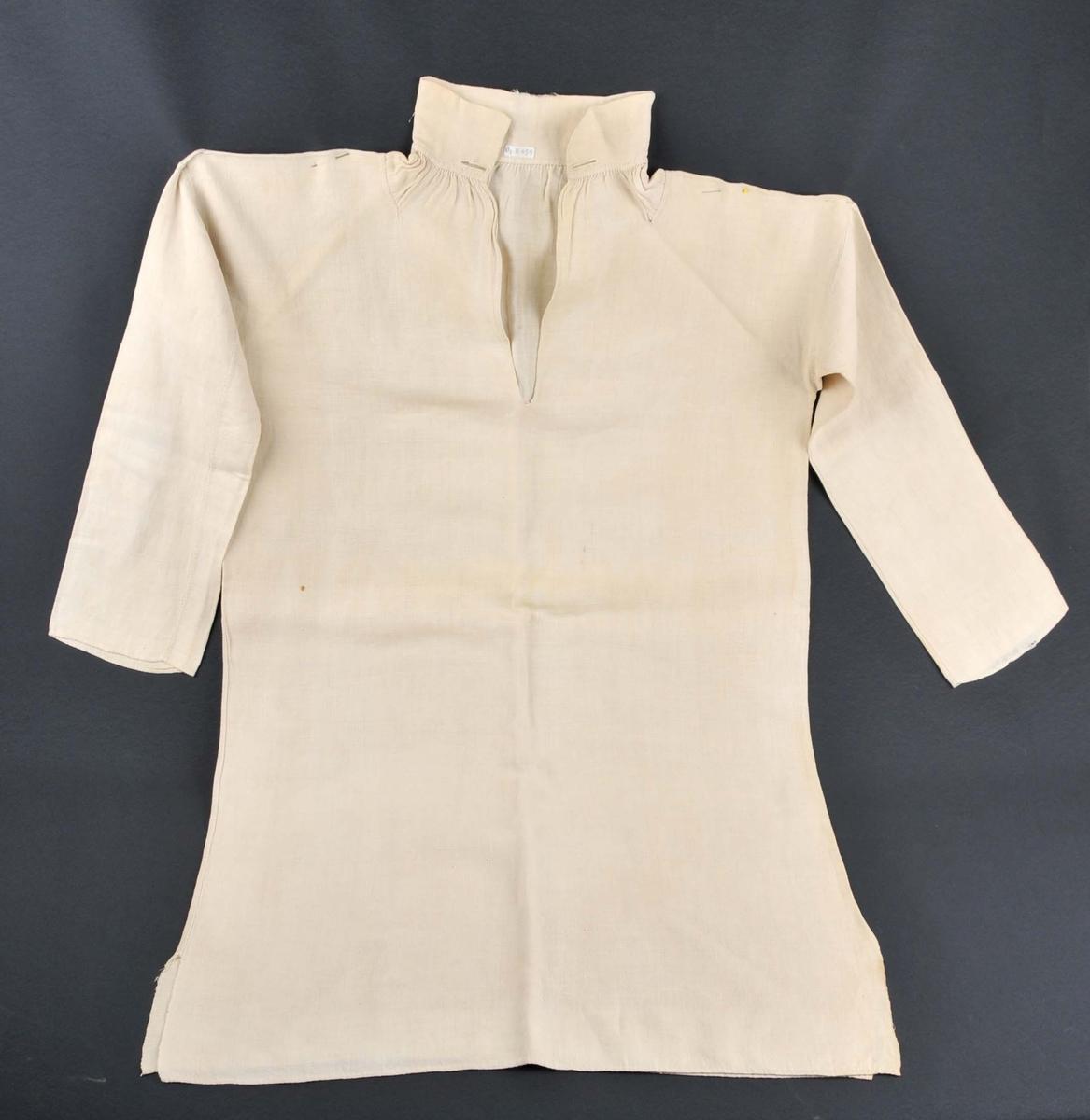 Handsydd herreskjorte med splitt midt framme. Bolbredda er lik vevbredda og er sydd saman med attersting. Skjorta har halslinning, skulderklutar, lask under armane og splitt i båe sider i nedre kant. Høgre arm er skøyta saman på langs av to stoffbredder. Armane og skuldestykka er samansydd med attersting, bretta smalt tilbake og sydd inntil med kastesting (=indresaum). To knapphol i begge endane, ein synleg rynketråd og  to rader med attersting nederst ved rynkinga på halslinnninga.
