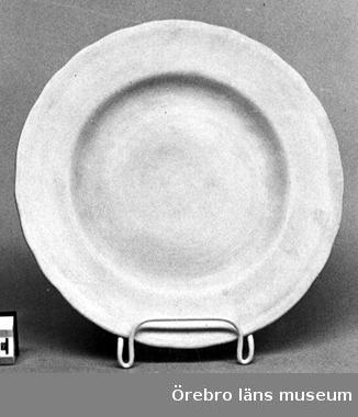 Diameter fotring: 152 mm.Flat, råämne. Ironstone China, Rörstrand. Tallriksämne, odekorerat och oglasert. Brämets ytterkant vågig. Stämplad i massan: Iron stone China, RÖRSTRAND MDCCCLX.Neg.nr.3830/79.