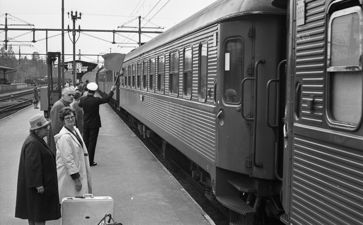 Frövi 2 juni 1967Resenärer i olika åldrar står på perrongen på Frövi järnvägsstation. Två äldre damer står i förgrunden. Den första damen bär en ljus hatt, mörk kappa, mörka skor samt glasögon. Den andra damen är klädd i vit kappa. En liten mörk resväska med ett paraply i samt en stor vit resväska står på marken mellan damerna. En stins står i bakgrunden och viftar med en flagga. Ett står vid perrongen.
