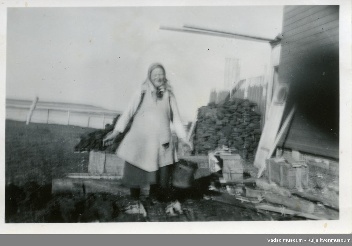 Grete Julkunen avbildet på baksiden av huset mens hun bærer en bøtte torv fra torvstabelen i bakgrunnen.