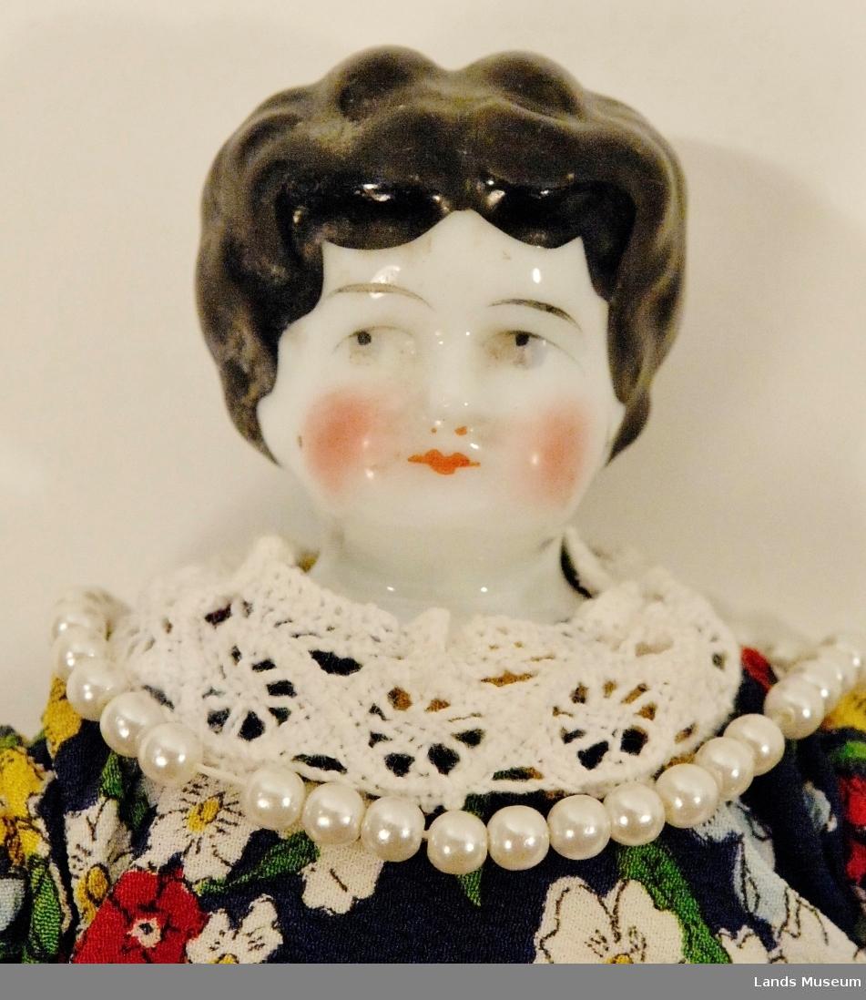 Dukke med porselenshovud og tøykropp. Hovudet er sydd på kroppen med lintråd. Dukken er sydd opp med rødt skjørt og ei bluse med blå grunngfarge og blomster som mønster. Blondekant på erme og hals. Dukken har også eit perlekjede, som truleg opprinnleg har vore eit armband.