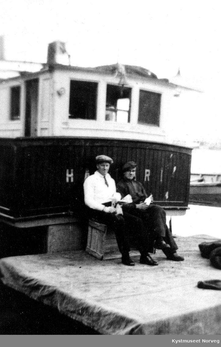 To mann sitter foran styrehus på båt.