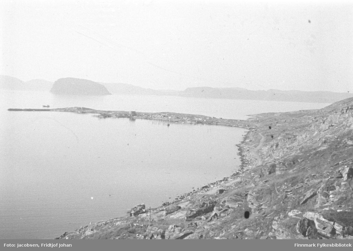 Bydelen Fuglenes i ruiner. Terrenget består stort sett av stein/berg, men litt lyng og gress ses spedt rundt. Fuglenesveien går langs Strandkanten fra Molla(ses ikke på bildet) og mot Fuglenesodden. Noen stolper står i området nær veien. Den lange, smale Fuglenesodden stikker ut i havet midt på bildet. To brakker er satt opp og utenfor moloen ses en fraktebåt. Utenfor molen ligger havområdet Sørøysundet med øya Håja som ses rett ovenfor enden av Fuglenesodden. Fjellpartiet i bakgrunnen er Sørøya. Bildet er tatt fra Mollafjell og det er nok et stykke utpå sommeren siden et par brakker er bygd.