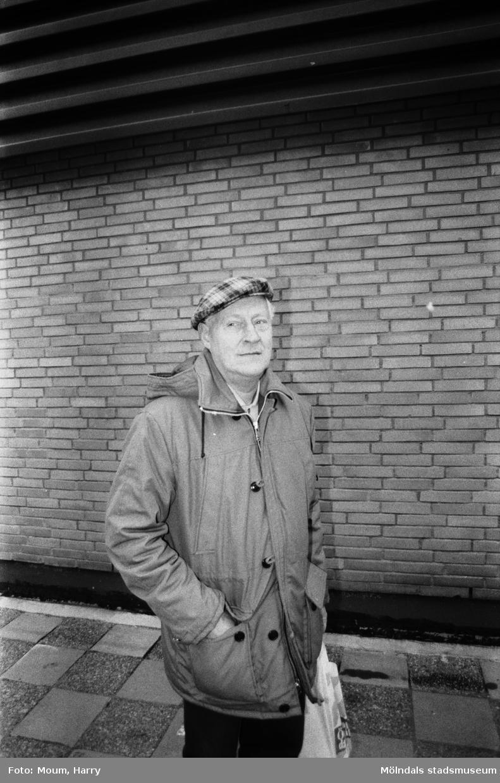 """Karl Erik Folin i Kållereds centrum, år 1983.  """"Vad tycks? Vi frågade i Kållered centrum var de brukade göra sina inköp.  Karl Erik Folin på väg hem till stugvärmen från en av Kållereds affärer. – Jag handlar faktiskt all här utom sådant som finns i specialaffärer. Idag har jag som exempel varit till Mölndal för att jag behövde något i bokhandeln där. Annars är Kållered billigt och bra, och så bor man ju här, dessutom. Det kostar att dra iväg några kilometer nu för tiden.""""  Fotografi taget av Harry Moum, HUM, för publicering till enkäten """"Vad tycks"""" i Mölndals-Posten, vecka 49, år 1983."""