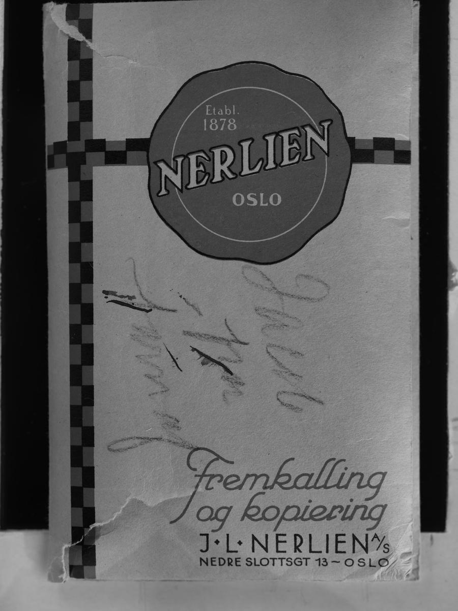 Konvolutt fra fotografen/ firmaet J.L. Nerlien AS, hvor 79 celluloseacetat negativer og to glassplater ble oppbevart.  Baksiden: Håndskrevet og trykket tekst.