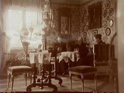 """""""Gamla hemmet"""", rumsinteriör, tre damer med handarbete.Från höger Anna Thermaenius med mamma Jenny.""""Gamla hemmet"""" var det första som familjen bosatte sig i när man flyttade från Torshälla till Hallsberg 1868. Det började byggas av Johan Thermaenius."""