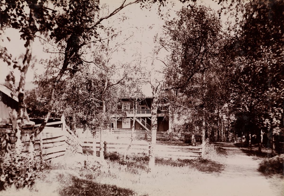 Et hus blant trær, på høyre siden en vei.