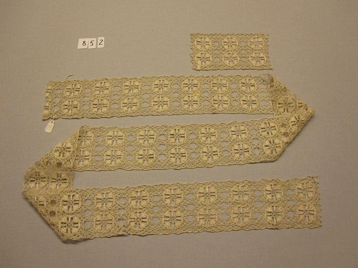 """Två knytprover/spetsprov av filéknutet nät med trätt mönster, knutet och trätt. Nät av rakställda rutor med tätare trädningar i stoppstygn vilka bildar genombrutna rundlar på singlad/glesare trädd botten. 1/4 -blekt 3-trådigt s-tvinnat lingarn i nät. Trädning i halvblekt lingarn.  852 :1  Mått 150 x 80 mm. Vidhängande lapp med texten: """"arbtsl ela"""" (litet svårt att se om det står """"ela""""). 852 :2  Mått 1490 x 750 mm. Vidhängande lapp med texten: """"15-"""" ( och två-treoläsliga bokstäver till)."""
