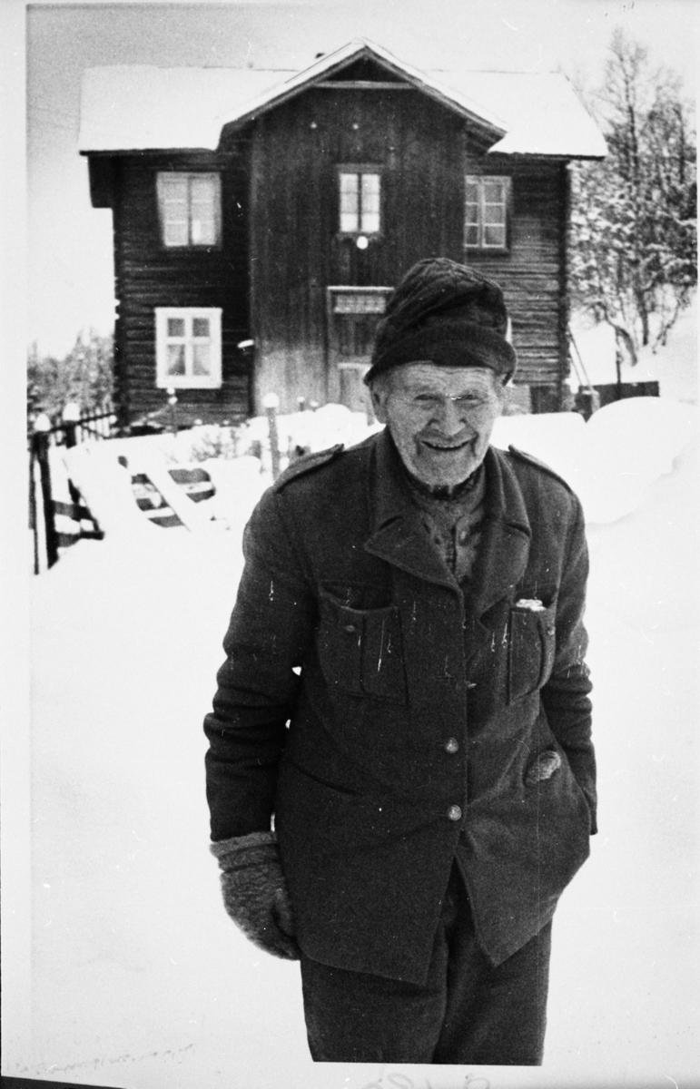 Portrett av en mann stående foran et hus. Mannen er iført lue og vinterklær.