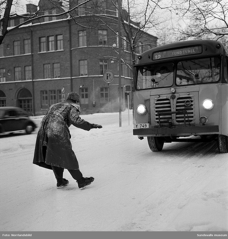 Bilinspektionen (föregångare till Svensk bilprovning) kontrollerar en buss på Skolhusallen. I bakgrunden gamla brandstationen.