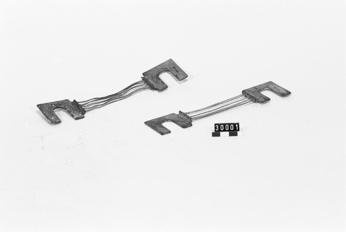 2 säkringar av koppar och silvertråd. 500 amp. säkring bestående av fem st. trådar av silver fastlödda i vardera änden vid en kopparplåt.