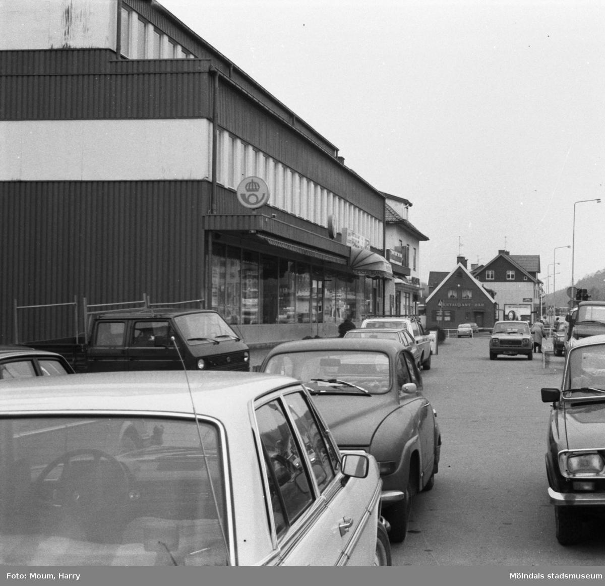 Parkerade bilar utanför posthuset vid Gamla Riksvägen i Kållereds centrum, år 1984.  För mer information om bilden se under tilläggsinformation.