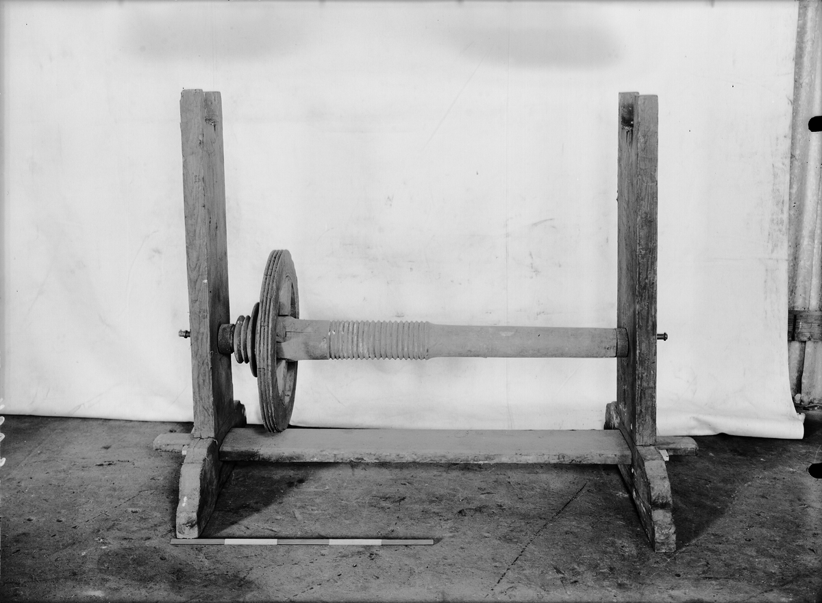 Stativ av trä med snörtrissa till maskin av obekant användning.