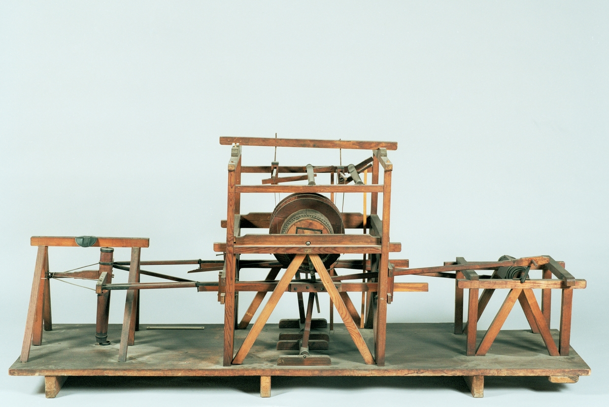 """Modell av uppfodringsverk, av Rudien. Text på föremålet: """"N:o 54.... XII.25."""". I Jonas Norbergs förteckning från 1779 beskrivs modellen på följande sätt: """"Modell på Upfordringsverk, af Herr Konstmästaren Rudeen."""""""
