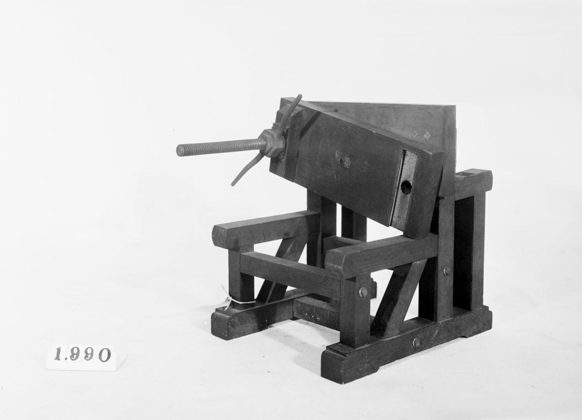 """Modell av press. Text på föremålet: """"F-?""""."""