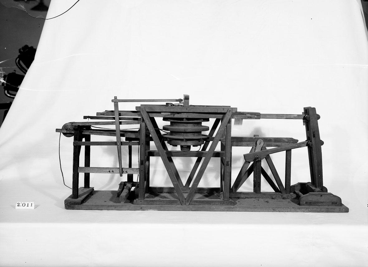 """Modell av uppfordringsverk. Text på föremålet: """"XII.32"""". I Jonas Norbergs förteckning från 1779 beskrivs modellen på följande sätt: """"Modell som visar, huru dubbla vefvar med stånggång nyttjas vid upfordringsvärck."""""""